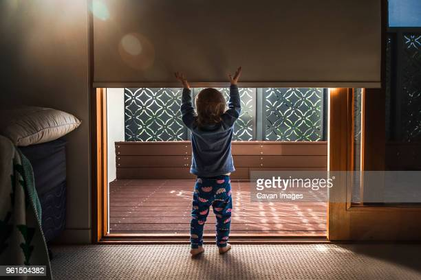 Rear view of baby girl with arms raised standing at entrance in house