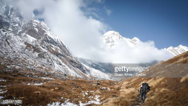 Rear View Of Backpack Man Hiking On Mountain During Winter