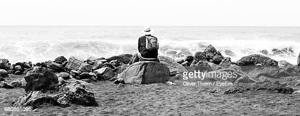 rear view of backpack man sitting on rock at beach - thiem foto e immagini stock