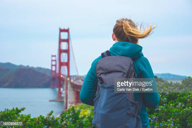 Rear View Of Backpack Woman Standing Against Golden Gate Bridge