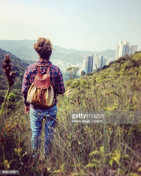 Rear View Of Backpack Woman Standing On Mountain
