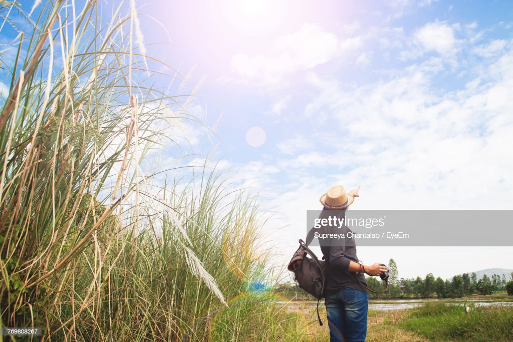 57ed3aff57 Rear View Of Backpack Woman With Camera Pointing Fingers In Sky   Stock  Photo