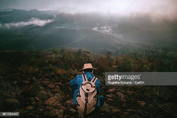Rear View Of Backpacker Crouching On Field
