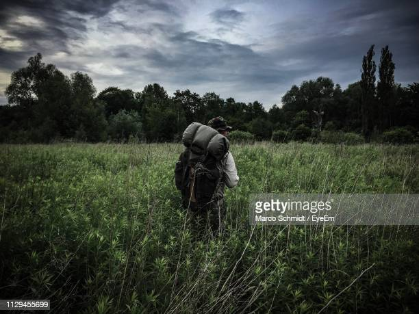 Rear View Of Backpacker Standing Amidst Plants On Field Against Cloudy Sky