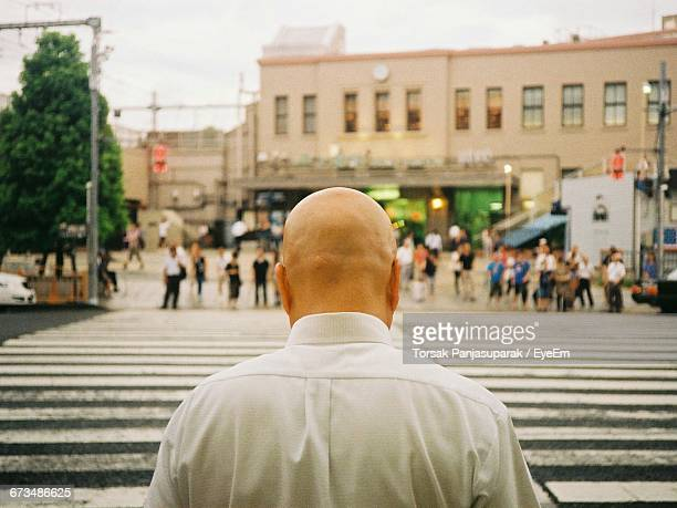 Rear View Of Bald Man Standing On Zebra Crossing In City