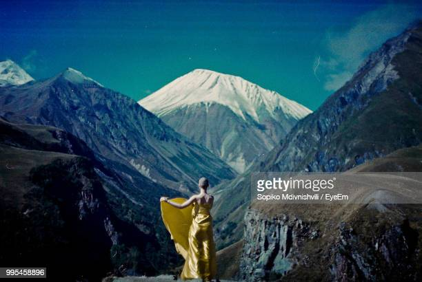 rear view of bald woman wrapped in yellow textile while standing against mountains - tbilisi bildbanksfoton och bilder