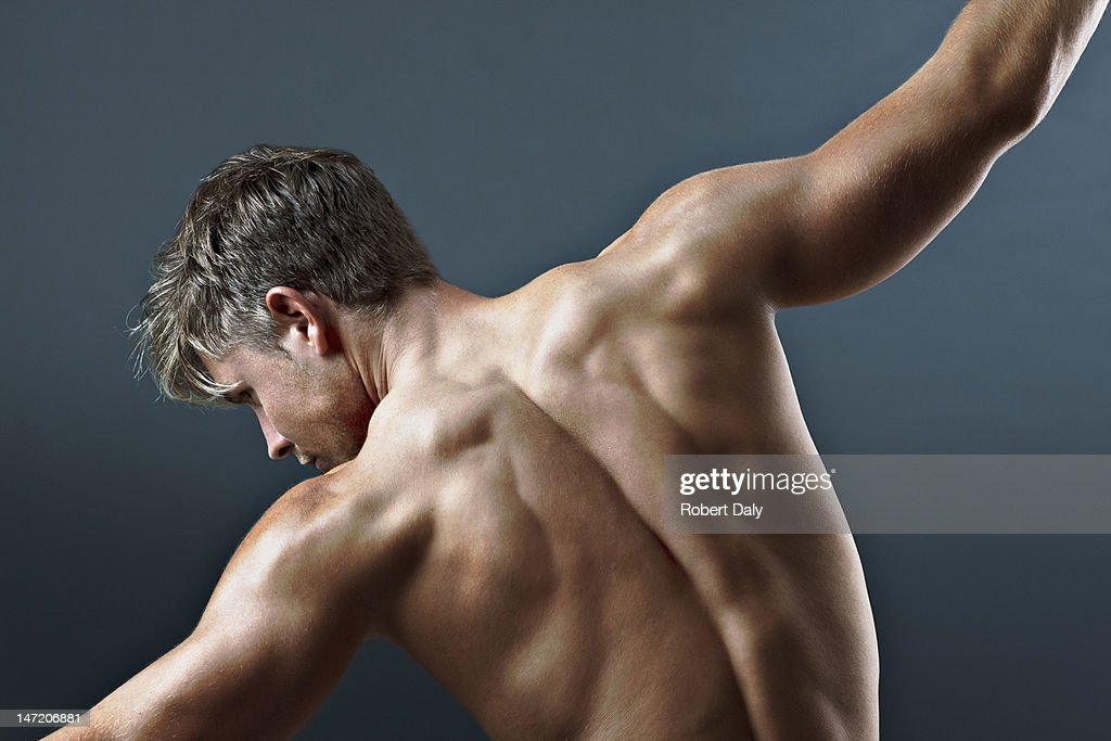 Rear view of bare chested man with arms outstretched : Stock Photo