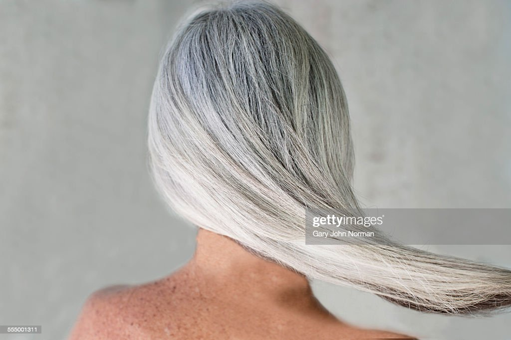 Rear view of bare shouldered mature woman with long grey hair : Stock Photo
