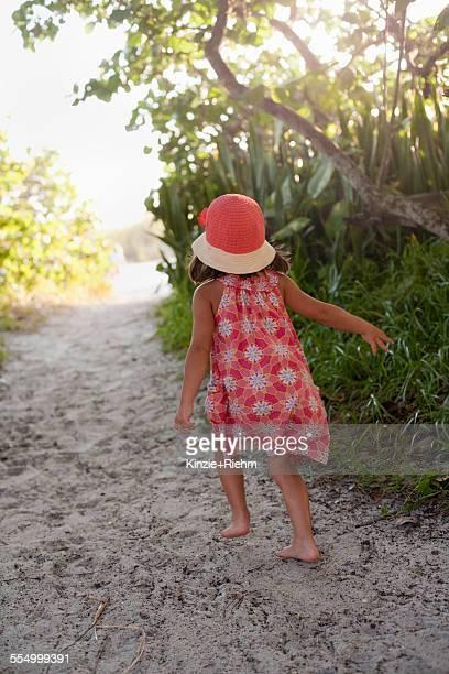 Rear view of barefoot girl in sunhat walking on woodland beach path, Anna Maria Island, Florida, USA