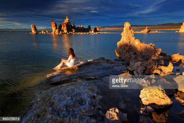 Rear view of barefoot woman in white dress sitting at Mono Lake shoreline at sunset, South Tufa, central California