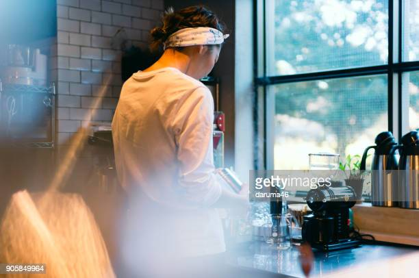 Rear View of Barista Making Coffee Machine at Cafe Counter
