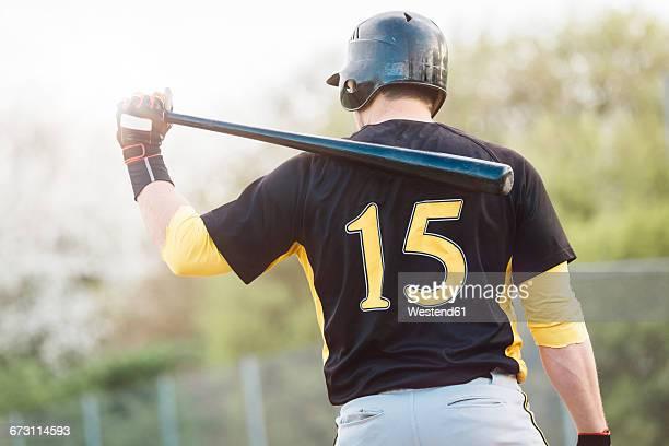 Rear view of baseball player holding bat