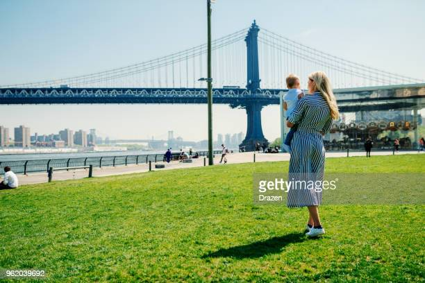 Rear view of beautiful blonde mother with baby girl in USA