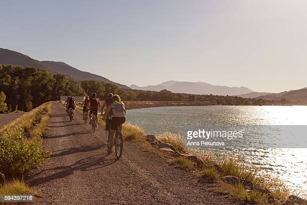 rear view of bike riders near lake ser-ponson, france - rivage photos et images de collection