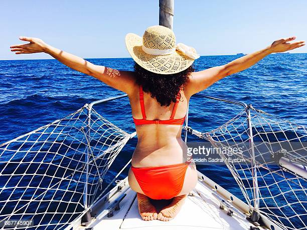 Rear View Of Bikini Woman With Arms Outstretched On Boat Deck Sailing In Sea