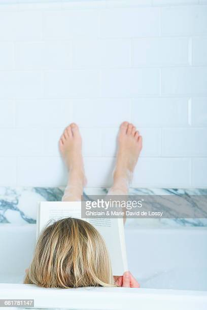 Rear view of blond haired girl reading a book in bath with feet up