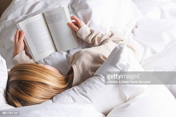 Rear view of blond haired girl reading book in bed