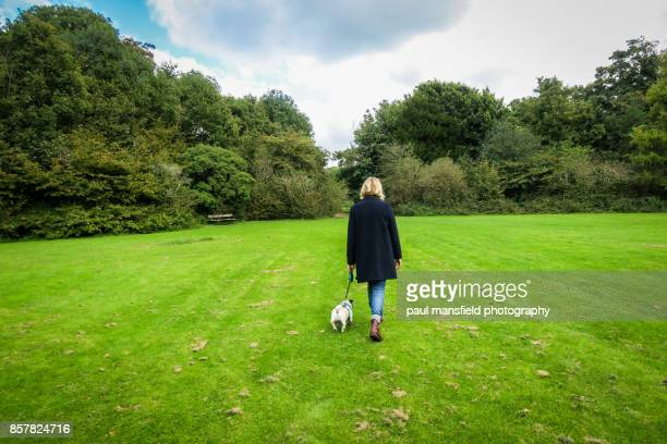 Rear view of blond lady taking her dog for a walk