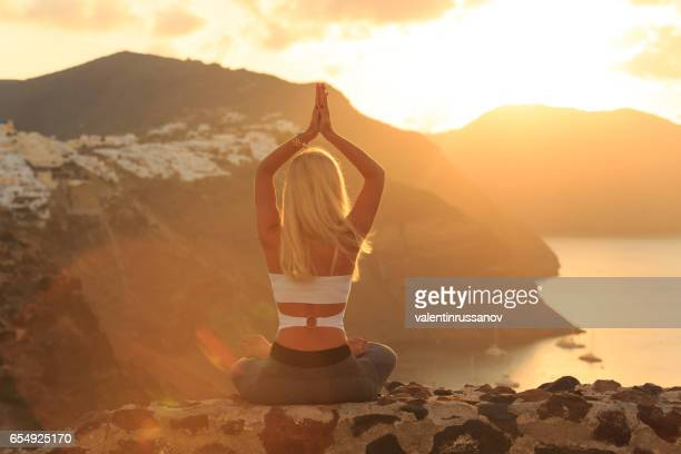 Rear view of blond woman practicing yoga in Santorini