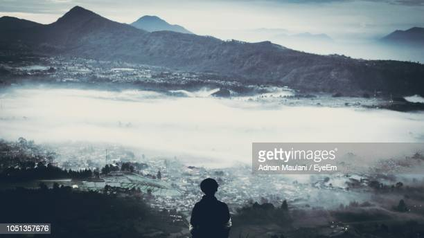 Rear View Of Boy Against Mountain During Foggy Weather