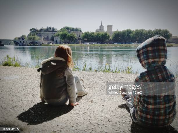 Rear View Of Boy And Girl Sitting On Riverbank Against Clear Sky