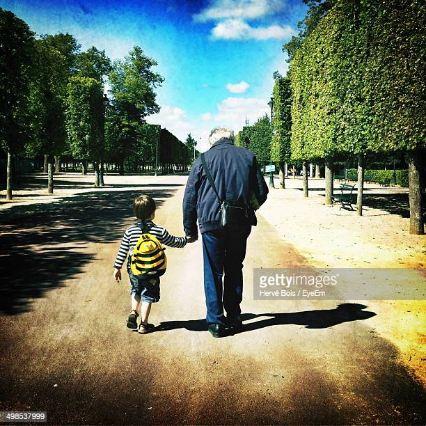 Rear view of boy and grandfather holding hands while walking on street