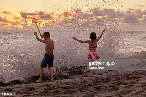 rear view of boy and sister playing in splashing waves at sunrise, blowing rocks preserve, jupiter island, florida, usa - blowing rocks preserve stock photos and pictures
