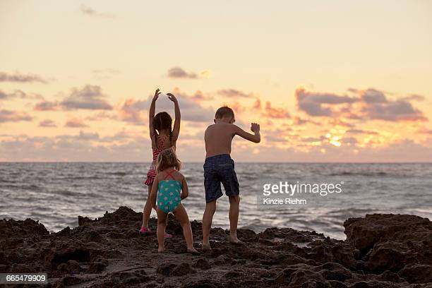 Rear view of boy and sisters playing on beach at sunrise, Blowing Rocks Preserve, Jupiter Island, Florida, USA