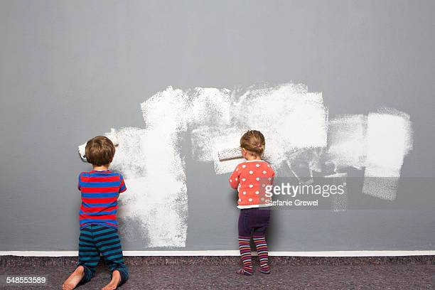 Rear view of boy and toddler sister painting wall