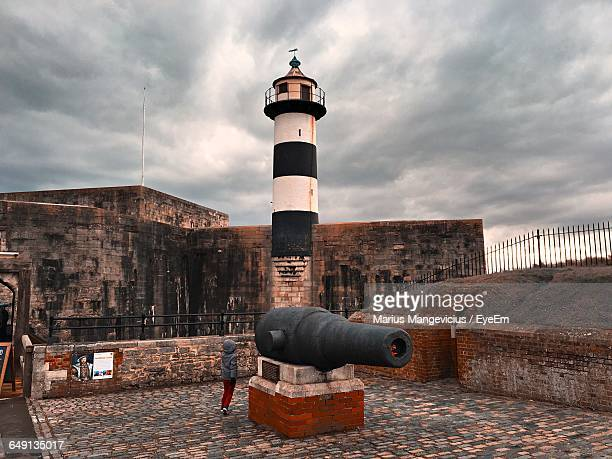 rear view of boy by cannon against cloudy sky at southsea castle - southsea stock pictures, royalty-free photos & images