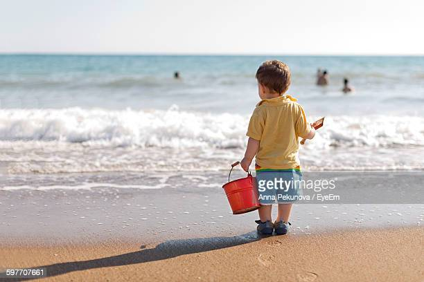 Rear View Of Boy Carrying Bucket At Beach