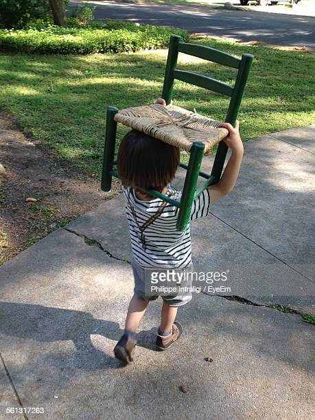 Rear View Of Boy Carrying Chair On Head Walking On Driveway