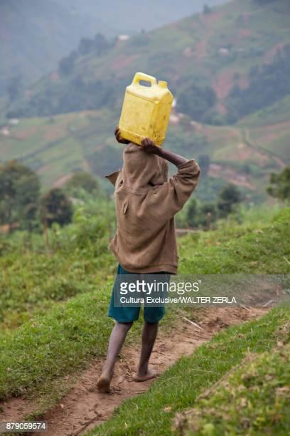 Rear view of boy carrying water container on head along rural path, Masango, Cibitoke, Burundi, Africa