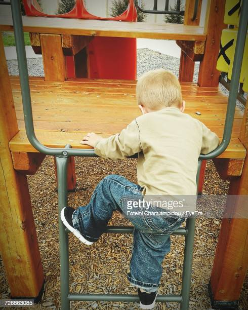 Rear View Of Boy Climbing On Play Equipment At Playground