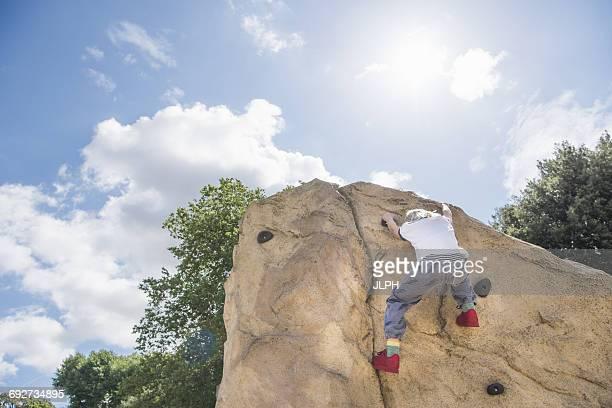 Rear view of boy climbing up climbing wall