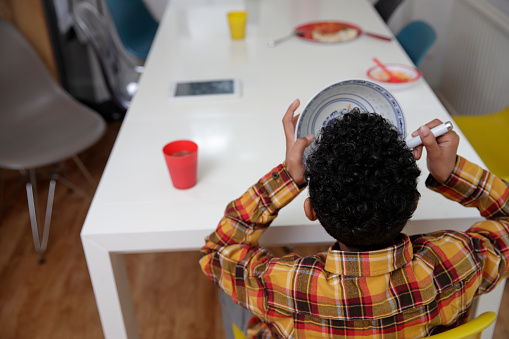 Rear view of boy eating breakfast at table - gettyimageskorea