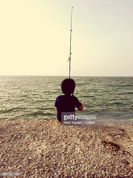 Rear View Of Boy Fishing In Sea While Sitting On Retaining Wall