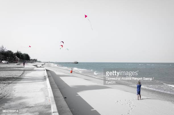 rear view of boy flying kite at beach against sky - isolated color stock pictures, royalty-free photos & images