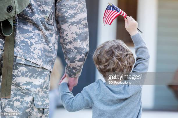 Rear view of boy holding hands with military dad