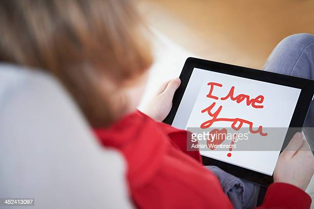 Rear view of boy holding tablet saying 'I love you
