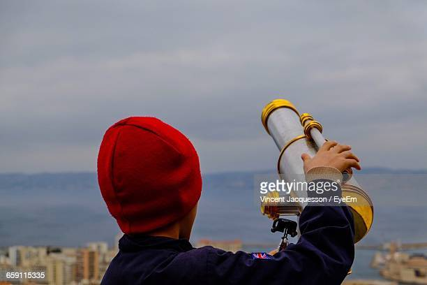 Rear View Of Boy Holding Telescope Against Sky