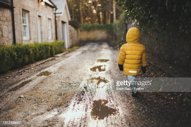 rear view of boy in yellow coat on small road - one boy only stock pictures, royalty-free photos & images
