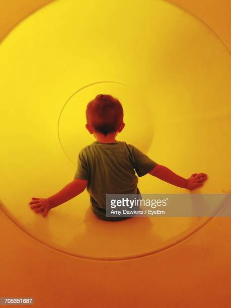 Rear View Of Boy In Yellow Tunnel At Playground
