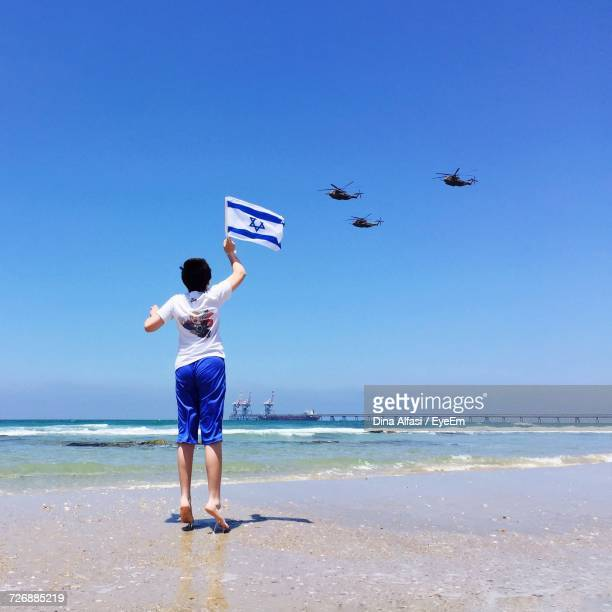 Rear View Of Boy Jumping With Israeli Flag While Looking At Military Helicopters Flying Over Beach