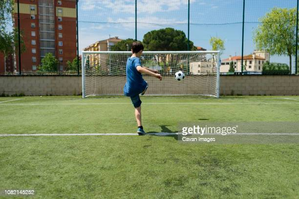 rear view of boy kicking soccer ball towards net on field - kicking stock pictures, royalty-free photos & images