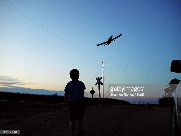 Rear View Of Boy Looking At Airplane Flying In Sky During Sunset