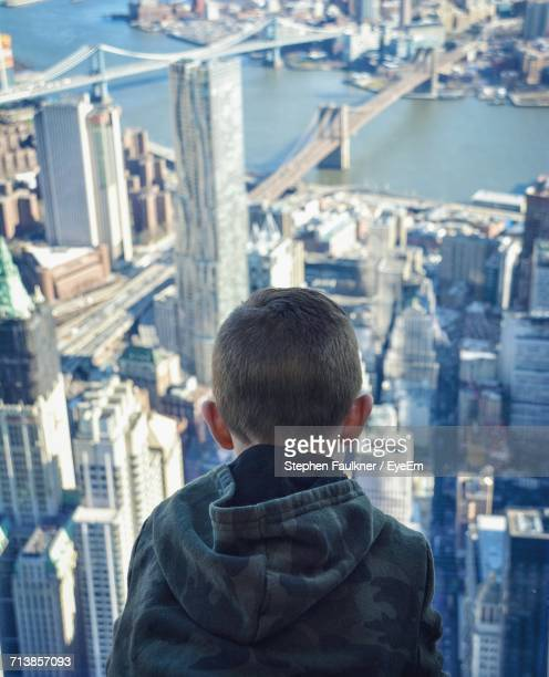 Rear View Of Boy Looking At City