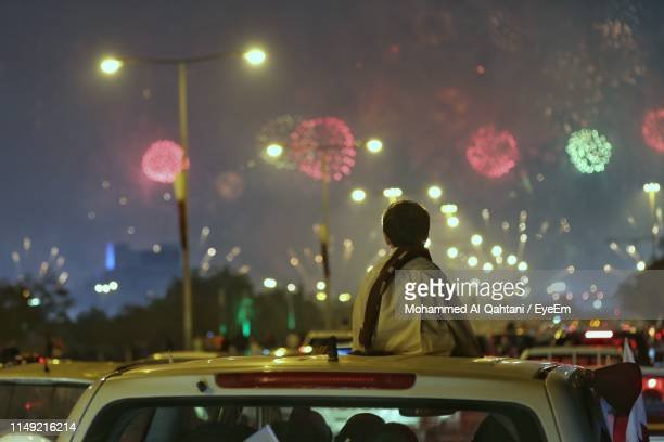 rear view of boy looking at firework display while sitting on car roof at night - childhood stock pictures, royalty-free photos & images