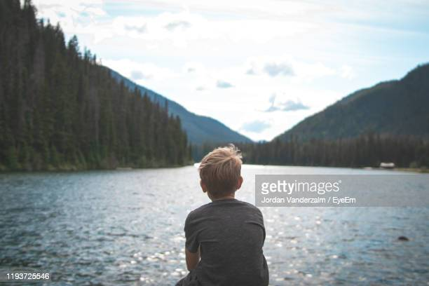 rear view of boy looking at lake against mountains - one boy only stock pictures, royalty-free photos & images