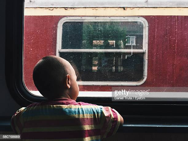 Rear View Of Boy Looking Out Of Window In Train